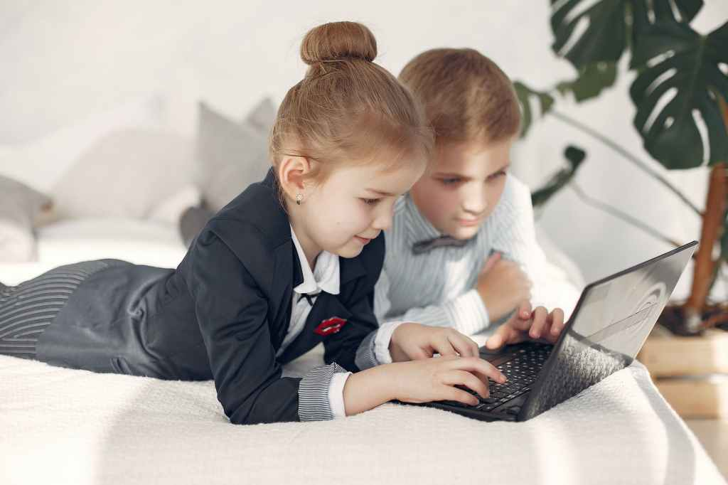children watching videos on laptop