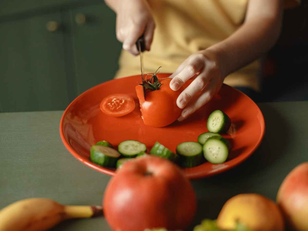 independent child cutting vegetables