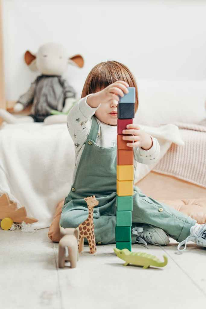 child building brick tower - fun activity to promote counting skills